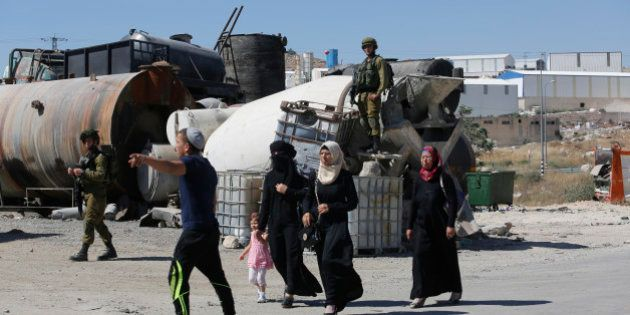 Israeli soldiers prevent Palestinian residents from crossing a security checkpoint at the closed entrance...