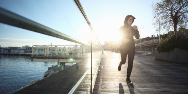Woman running at morning in Genoa port