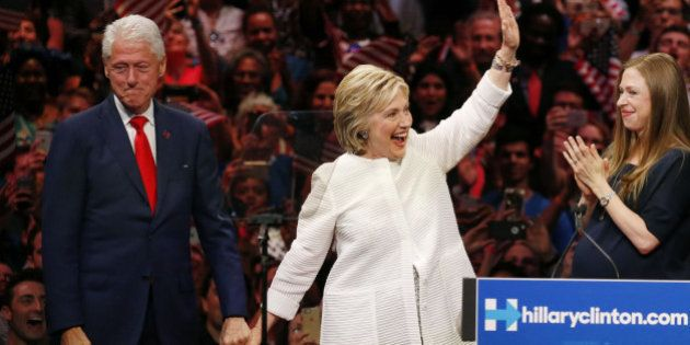 Democratic U.S. presidential candidate Hillary Clinton waves as she stands onstage with her husband former...