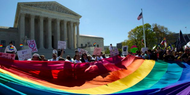 FILE - In this April 28, 2015, file photo, demonstrators stand in front of a rainbow flag of the Supreme...