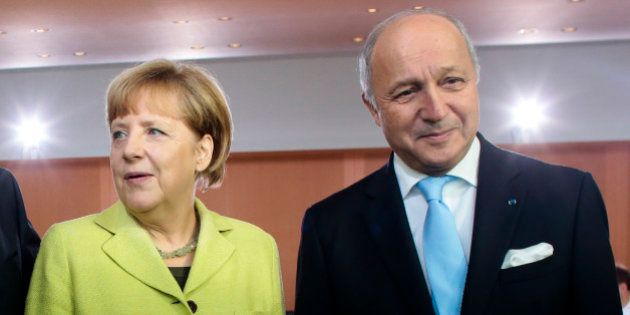 German Chancellor Angela Merkel, left, welcomes French Foreign Minister Laurent Fabius, right, for the...