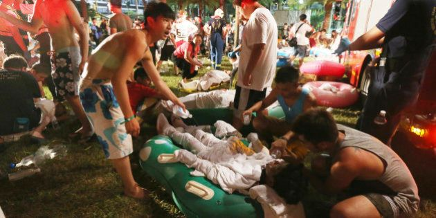 Emergency rescue workers and concert spectators tend to injured victims from an explosion during a music...
