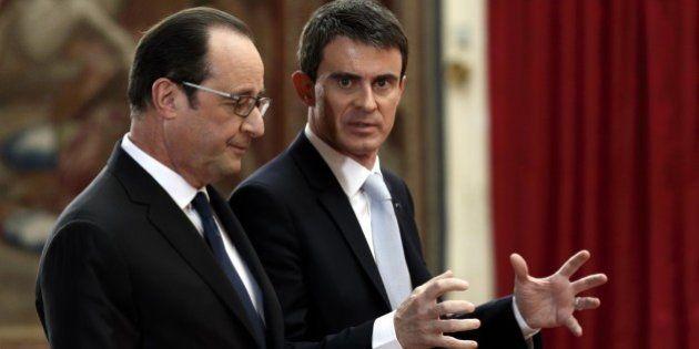 French President Francois Hollande, left, and French Prime Minister Manuel Valls leave after Hollande's...
