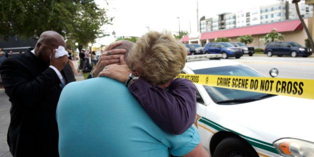 Terry DeCarlo, executive director of the LGBT Center of Central Florida, center, is comforted by Orlando...