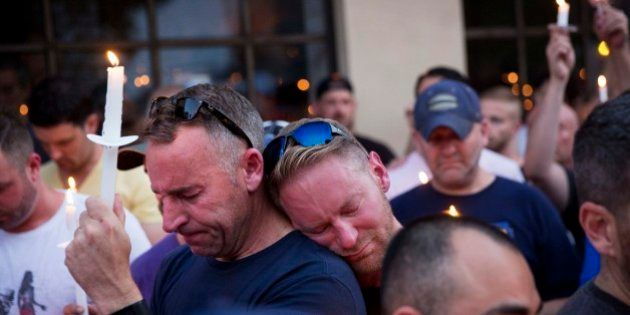 Paul Cox, right, leans on the shoulder of Brian Sullivan, as they observe a moment of silence during...
