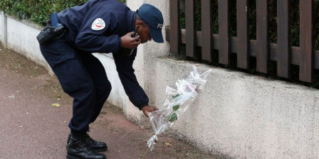 A French police officer lays flowers while paying tribute to his colleagues killed in a knife attack...
