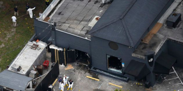 Police forensics investigators work at the crime scene of a mass shooting at the Pulse gay night club...