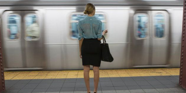 Caucasian woman standing near passing subway in train station