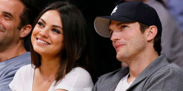 Actress Mila Kunis, left, and actor Ashton Kutcher, right, sit courtside together at the NBA basketball...