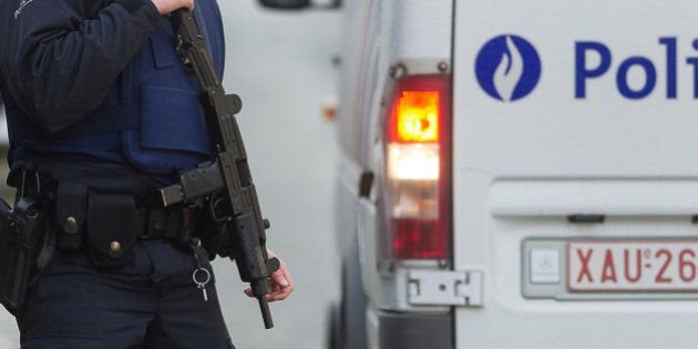Armed police secure an area in Brussels Tuesday March 15, 2016, after police launched an anti-terror...
