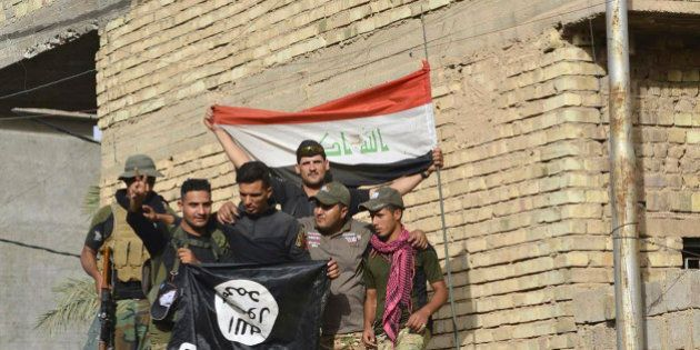 Iraqi security forces raise an Iraqi flag as they hold a flag of the Islamic State group they captured...