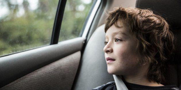 Boy (9 in backseat of car, looking out window