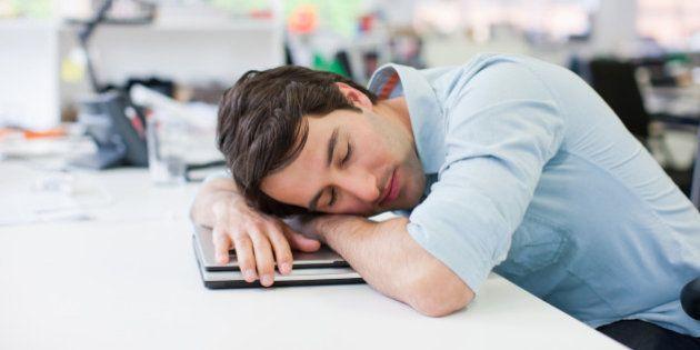 Businessman sleeping on laptop at desk in office