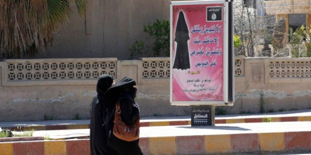 Veiled women walk past a billboard that carries a verse from Koran urging women to wear a hijab in the...