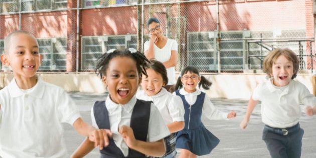 Multi-ethnic school children running from teacher