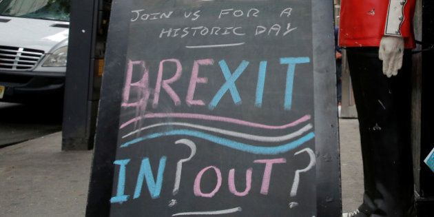 Children pose next to a chalkboard advertising a Brexit viewing event