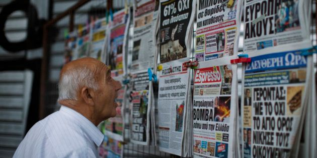 A man looks at the newspapers at a newsstand in central Athens, Monday, July 6, 2015. Greece's finance...