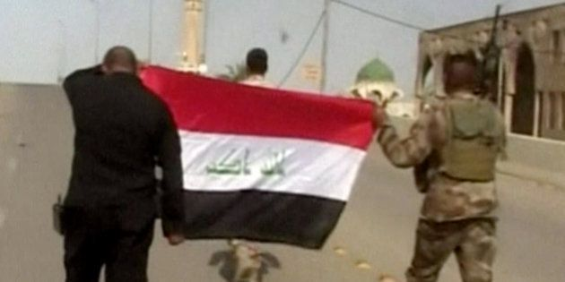 This image made from Associated Press video shows, Iraqi soldiers carrying an Iraqi flag to hoist on...