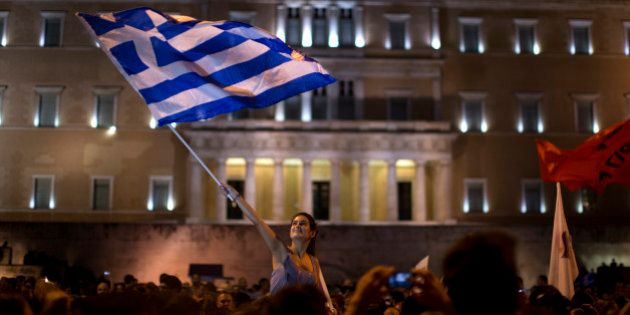 A supporter of the No vote waves a Greek flag in front of the parliament after the results of the referendum...