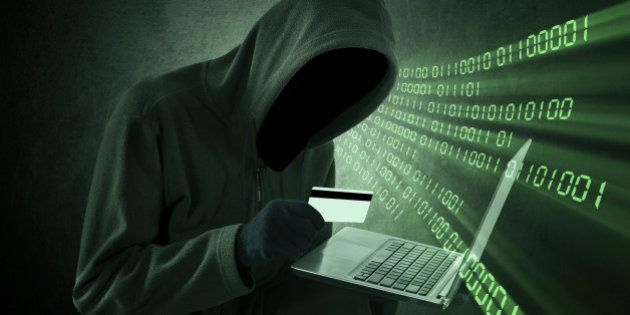 Internet theft concept - Man holding credit card with laptop on his