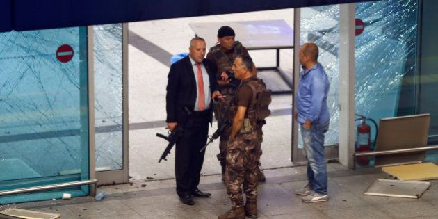 Armed security stand at an entrance of Turkey's largest airport, Istanbul Ataturk, Turkey, following...