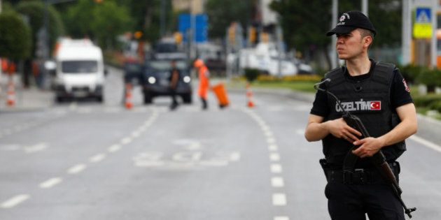 A police officer stands guard near the site where a Turkish police bus was targeted in a bomb attack...