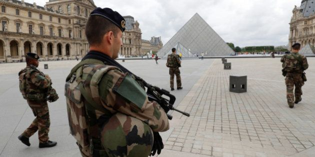 French army soldiers patrol near the Louvre Museum Pyramid's main entrance in Paris, France, June 13,...