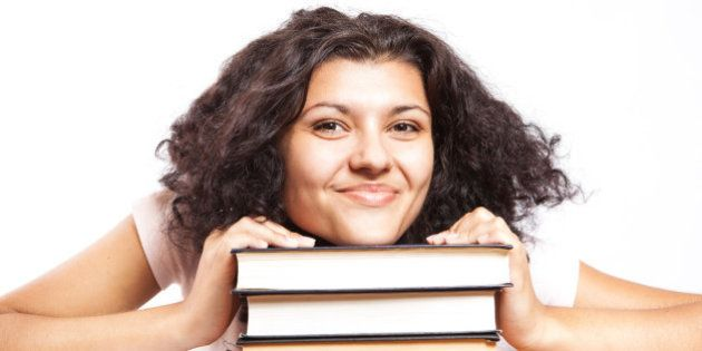 A university student with her head on her books giving a big