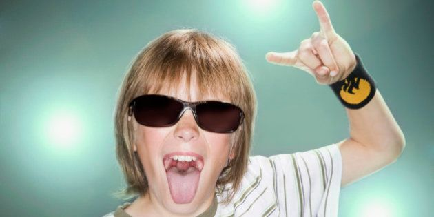 Boy with sunglasses making horn gesture