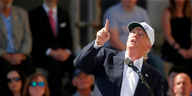 Republican presidential candidate Donald Trump points to an airplane passing overhead at a town hall-style...