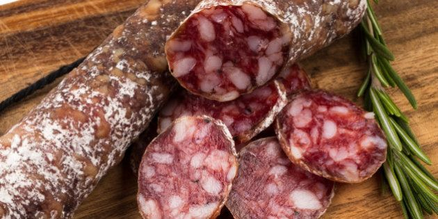 slices of salami on a wood board as a background