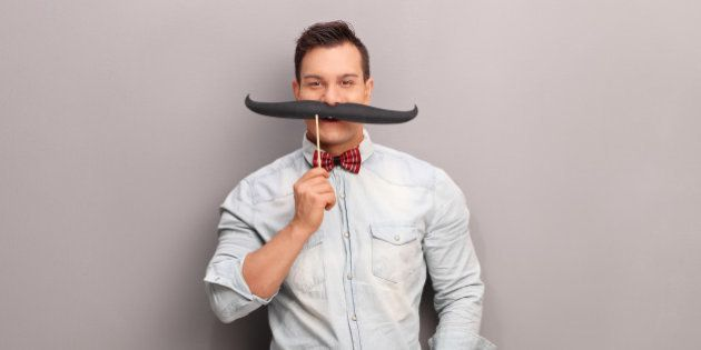 Cheerful young man holding a huge fake moustache below his nose and looking at the camera