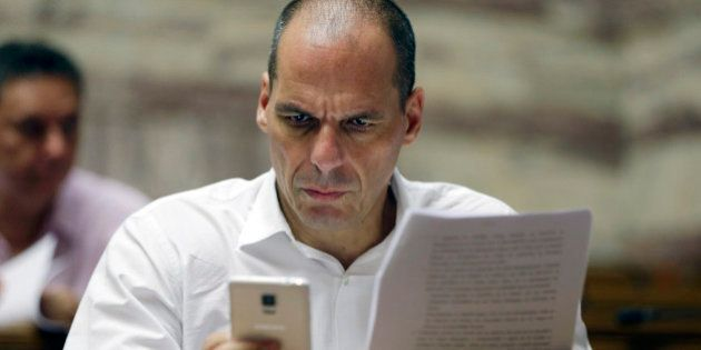 Parliament member Yanis Varoufakis checks his cell phone before a meeting with lawmakers of Syriza party...