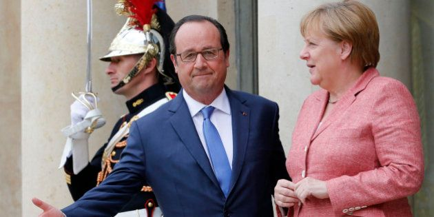 French President Francois Hollande (L) welcomes German Chancellor Angela Merkel as she arrives to attend...