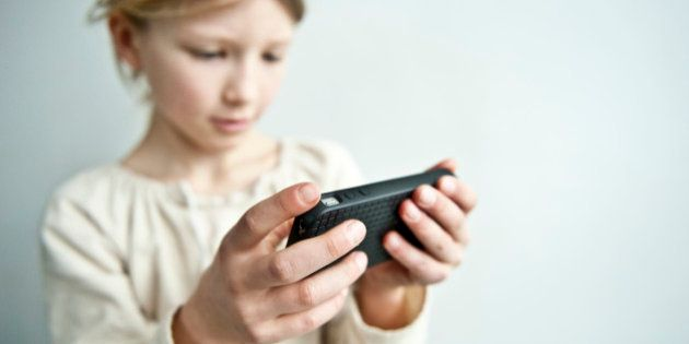 young girl plays with a cell phone