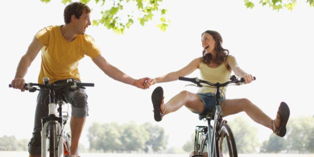 Happy couple riding bicycles and holding