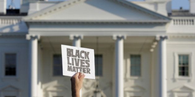 A demonstrator with Black Lives Matter holds up a sign during a protest in front of the White House in...