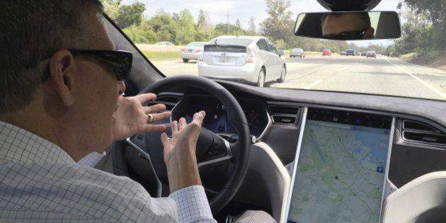 Reuters journalist Paul Ingrassia sits in the drivers seat of a Tesla S-Type in Autopilot mode in San...