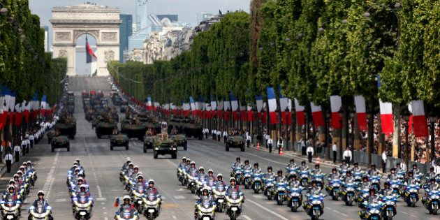 French gendarmerie and police motorcyclists ride in formation down the Champs Elysee avenue during the...