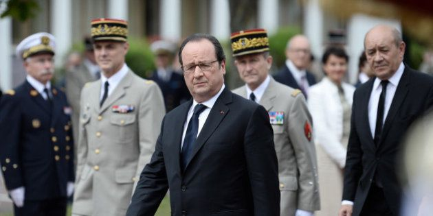 French President Francois Hollande (front C) walks ahead of French defence Minister Jean-Yves Le Drian...