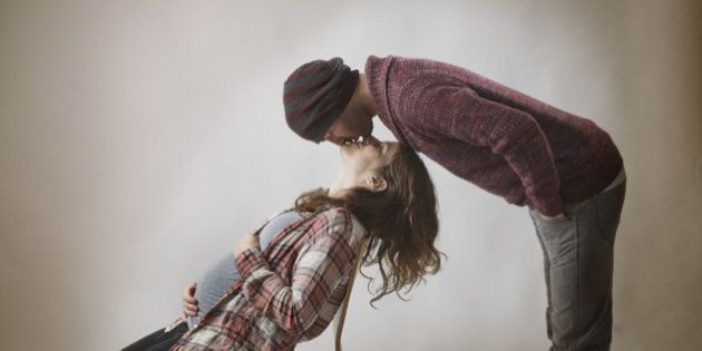 PRegnant couple in chair and kissing