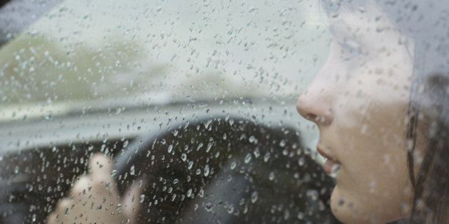 A woman driver sitting in car looking out window, raindrops on window
