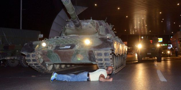 A man lays in front of a tank in the entrance to Istanbul's Ataturk airport, early Saturday, July 16,...
