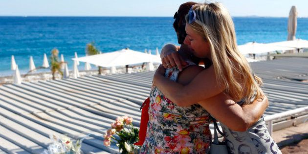 Women react at the site of a deadly truck attack on the famed Promenade des Anglais in Nice, southern...