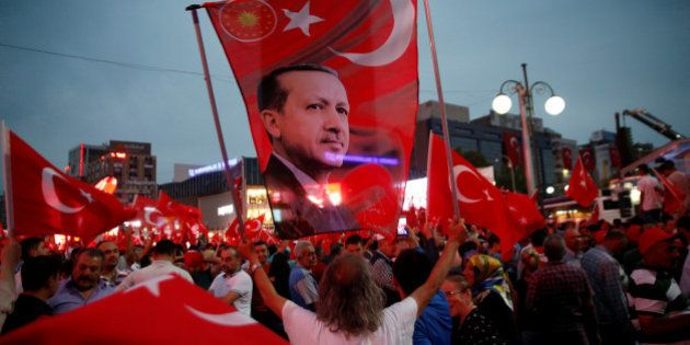 A supporter holds a flag depicting Turkish President Tayyip Erdogan during a pro-government demonstration...