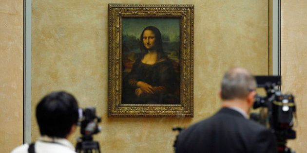 Members of the media are gathered next to the Mona Lisa, during an event to unveil the new lighting of...
