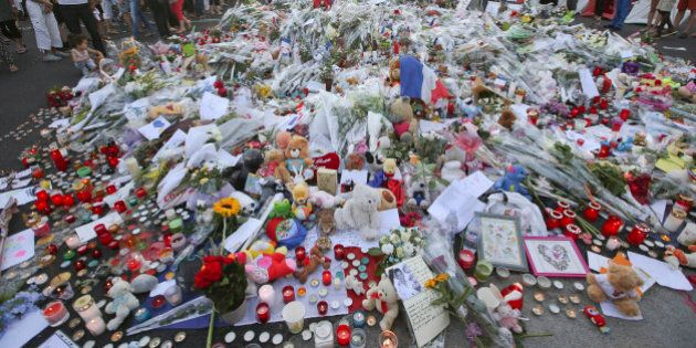 People gather at a makeshift memorial to honor the victims of an attack near the area where a truck mowed...