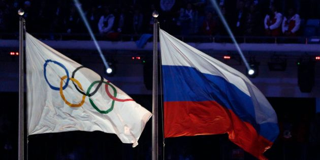 FILE- In this Feb. 23, 2014, file photo, the Russian national flag, right, flies after next to the Olympic...