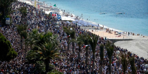 A general view shows the crowd gathering on the Promenade des Anglais during a minute of silence on the...