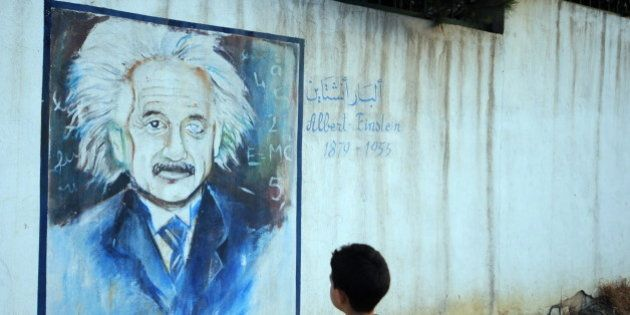 A boy looks at a wall showing a graffiti painting of Albert Einstein in Tunis, on July 11, 2010. AFP...